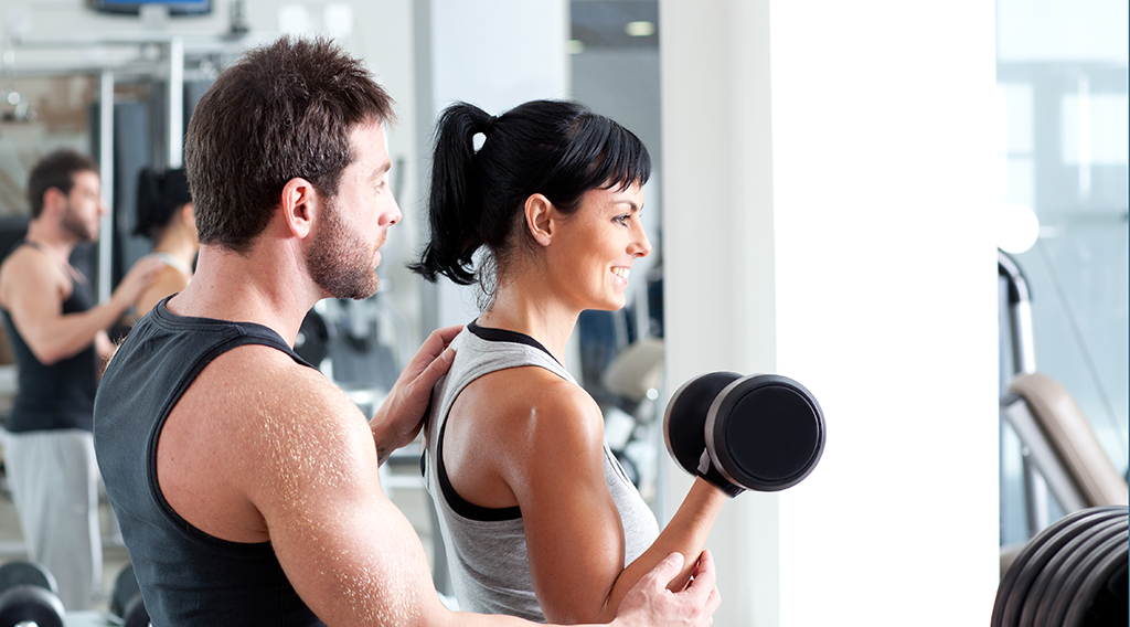 Personal trainer coach client in the gym with Virtuagym