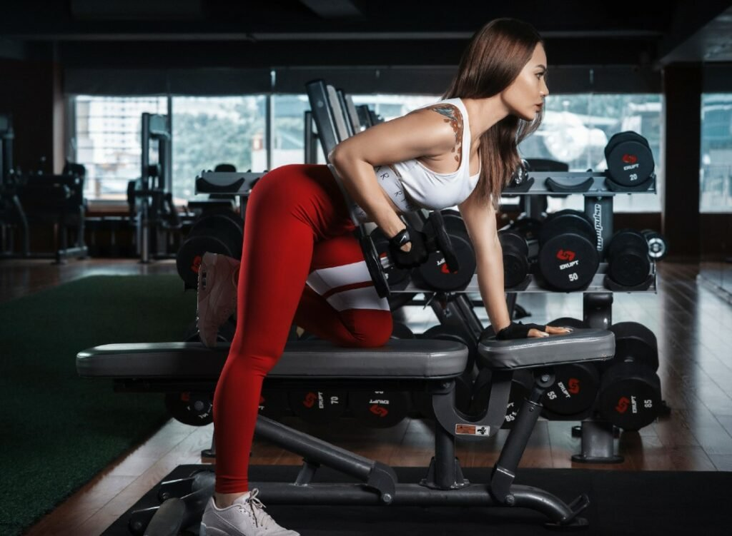 working out in a gym red leggings arms workout